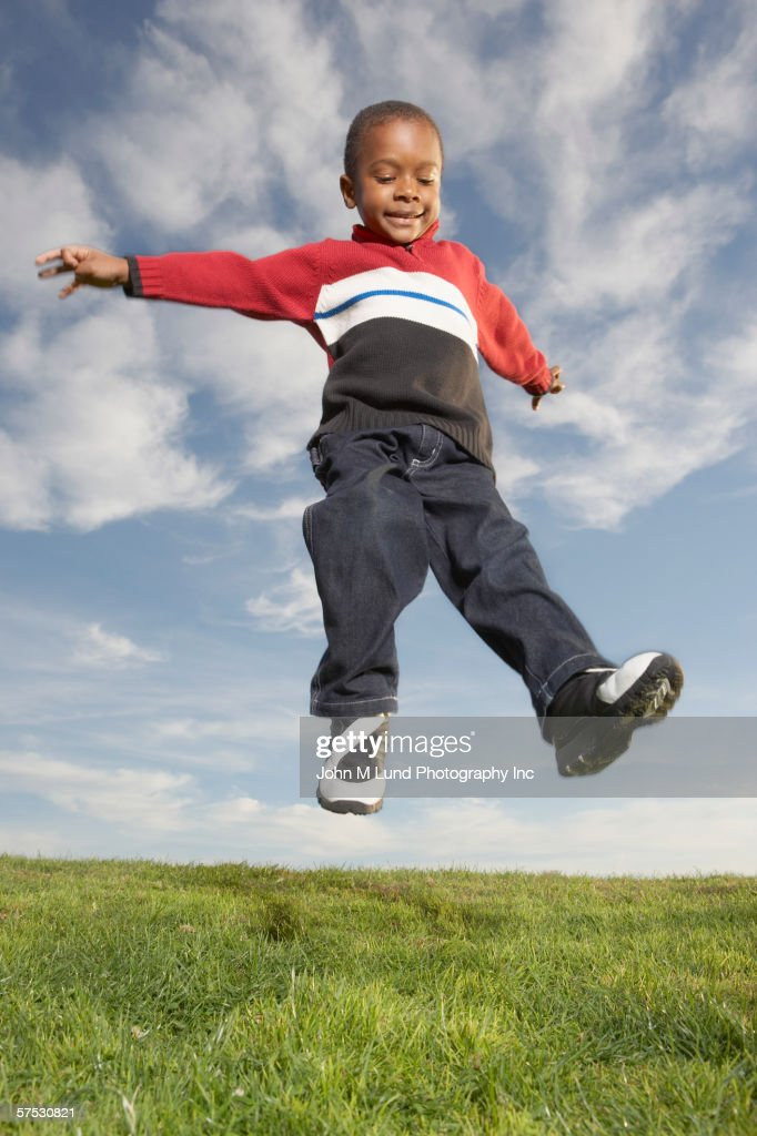 young boy jumping for joy stock photo getty images