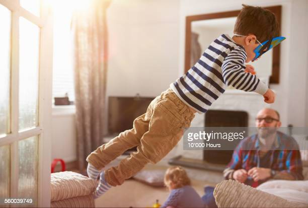 A young boy jumping from one sofa to another