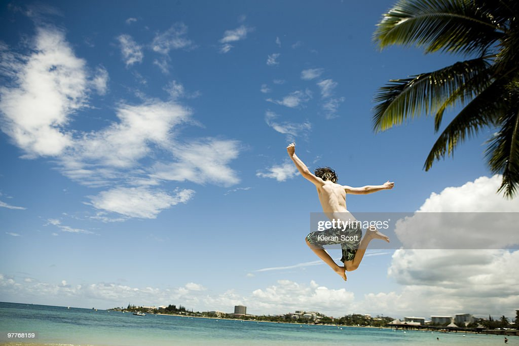 Young boy jumping in front of town by ocean. : Stock Photo