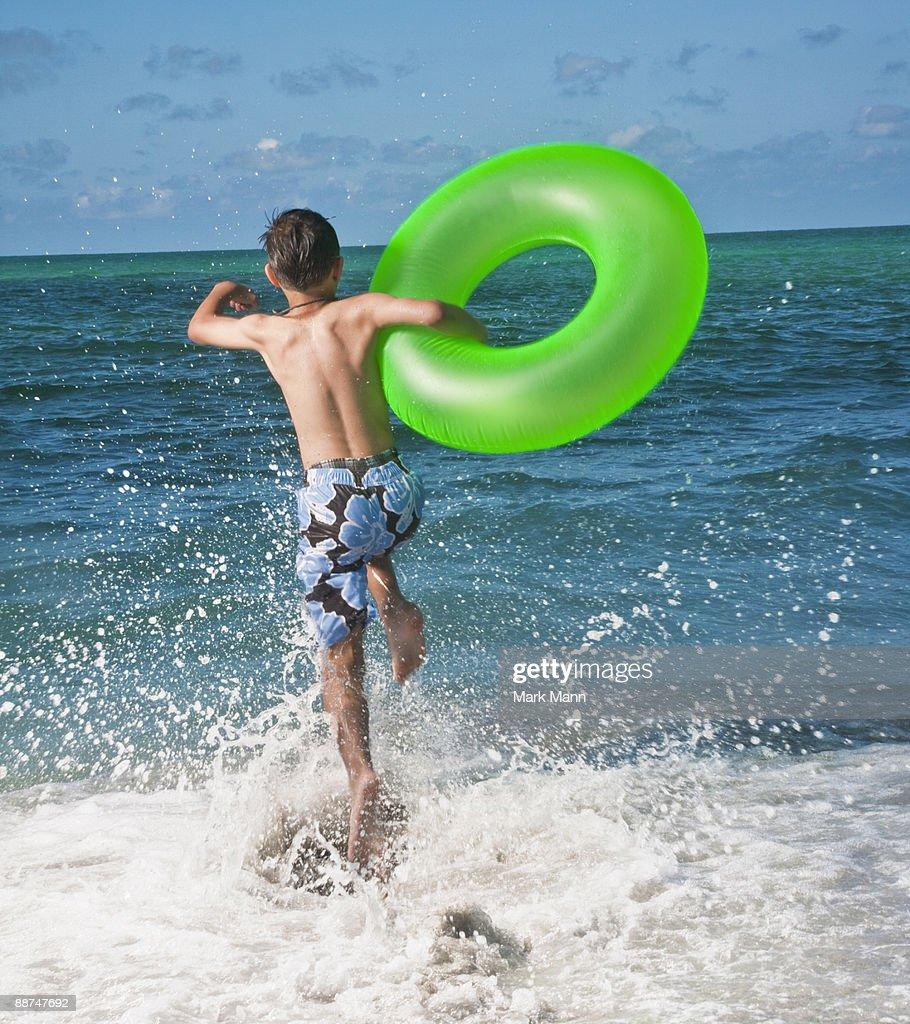 Young boy jumping in the waves. : Stock Photo
