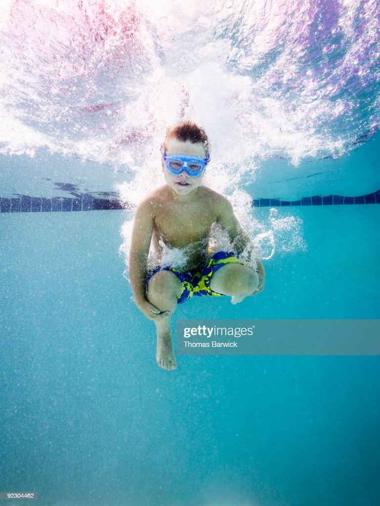 Pool Splash Cannonball young boy jumping into pool doing cannon ball stock photo | getty