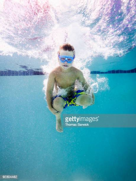 Young boy jumping into pool doing cannon ball