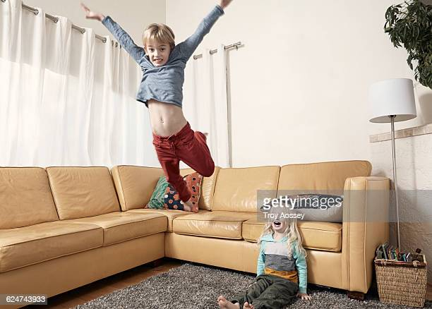 Young boy jumping off couch with little brother.