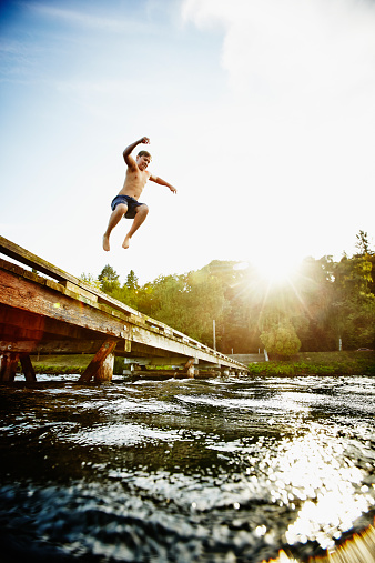 Young boy jumping off of dock into lake