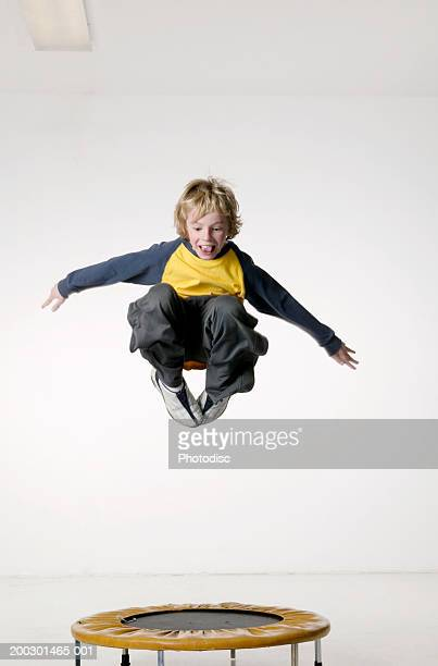 Young boy (8-9) jumping on small trampoline