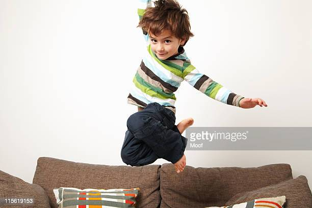 Young boy jumping on sofa
