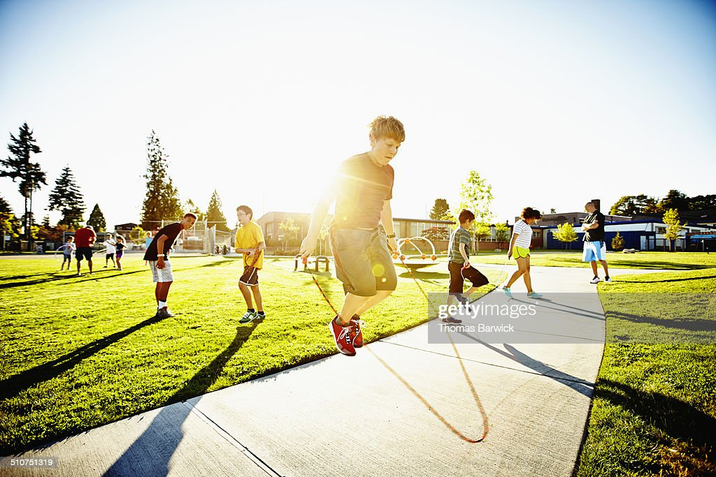 Young boy jumping rope on playground near school