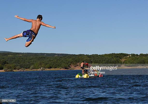 A young boy jumps for fun and relief off at 'Pita beach' in Soria north of Spain where high temperatures reached up to 35º degrees during the...