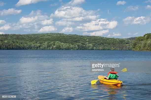 Young Boy Kayaking On Beautiful Lake