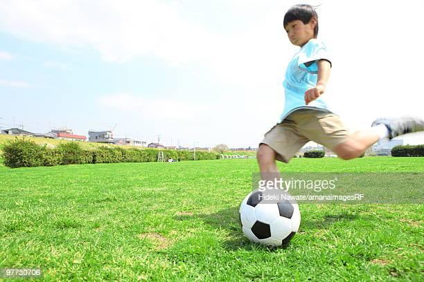 Young boy kicking soccer ball on field. Futako-tamagawa, Setagaya-ku, Tokyo Prefecture, Japan