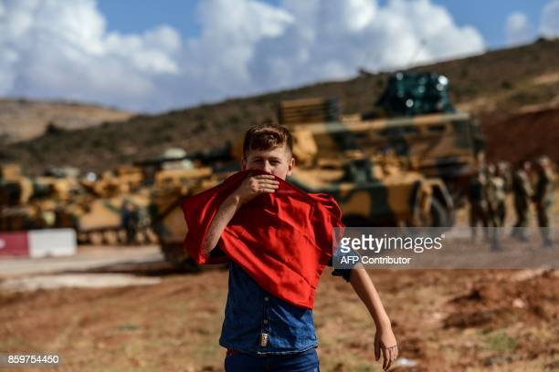 A young boy kisses a Turkish national flag as he stands near Turkish soldiers and armoured vehicles during a demonstration in support of the Turkish...