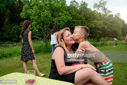 Young boy kissing mother at family reunion outdoors. : Stock Photo