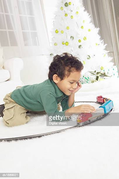 Young Boy Kneeling on the Floor of a White Living Room Playing with a Toy Train Set, at Christmas