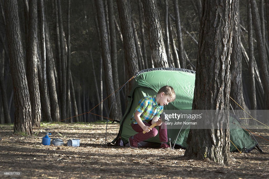 Young boy knocking in tent pegs