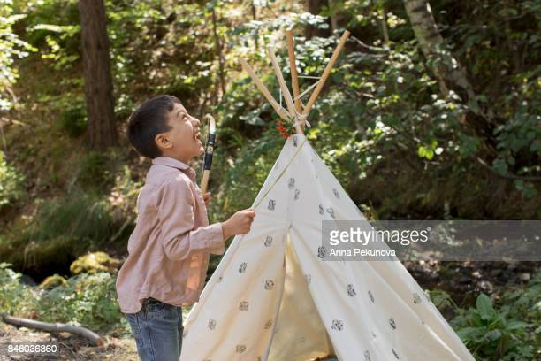 Young boy laughing happily in front of a teepee
