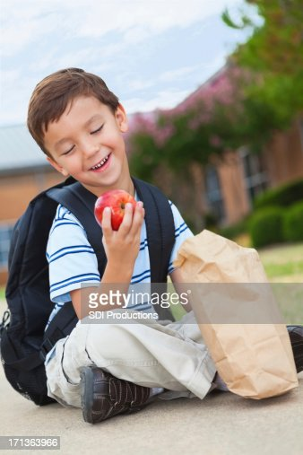 Young boy laughing while looking at his school lunch