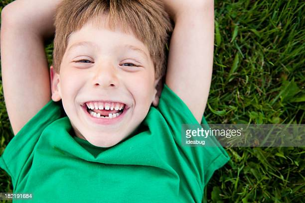 Young Boy Laughing while Lying in the Grass