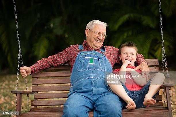 Junge Lachen mit seinem Großvater auf Schaukel