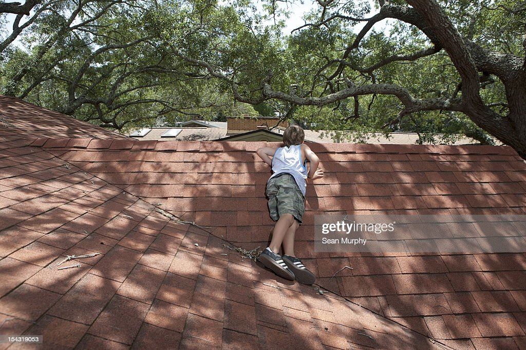 Young Boy Laying on a Roof : Stock Photo