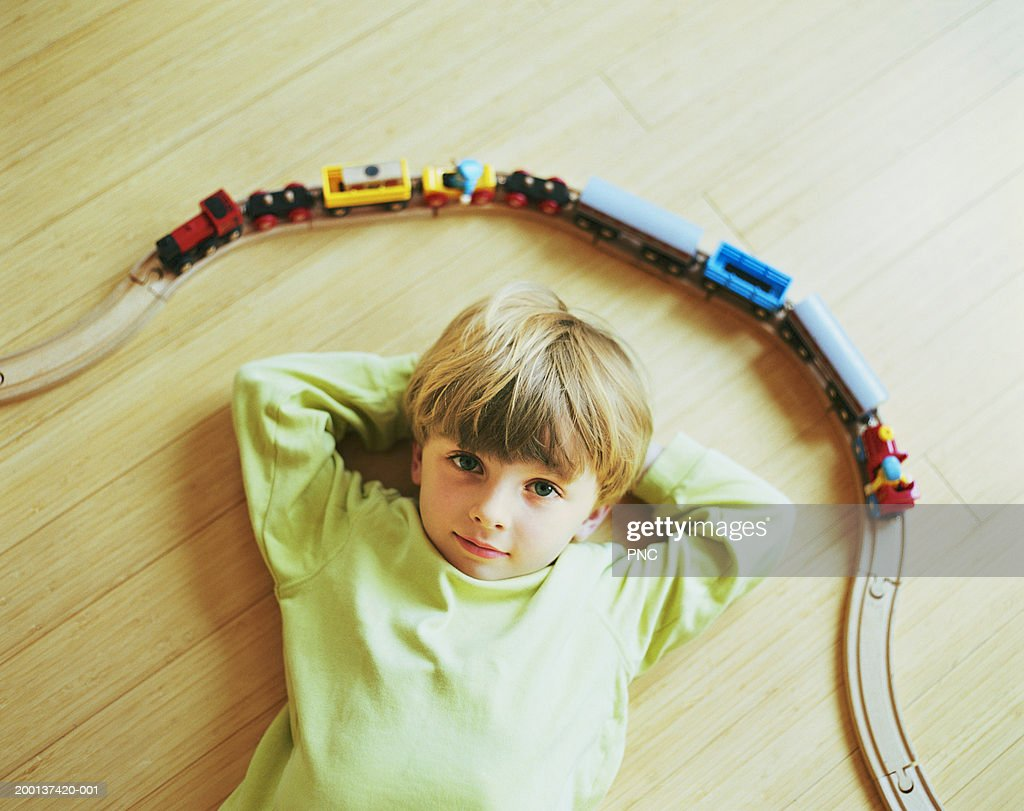 Young boy (3-5) laying on floor by toy train (elevated view)