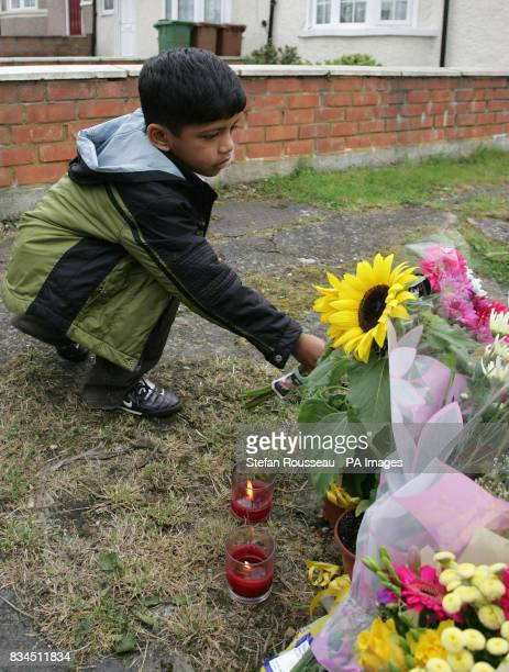 A young boy lays flowers outside Number 111 Park Lane in Carshalton where a fiveyearold boy and a fouryearold girl have died after being found with...