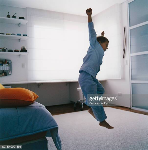 Young Boy Leaping Off Bed