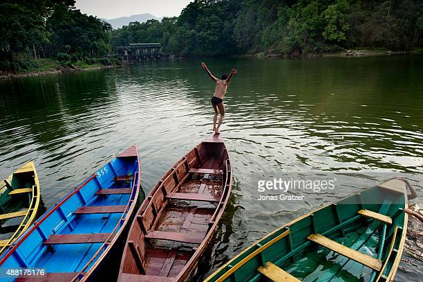A young boy leaps from the front of the boat as he dives into the lake Phewa Lake is a freshwater lake in Nepal located in the south of the Pokhara...