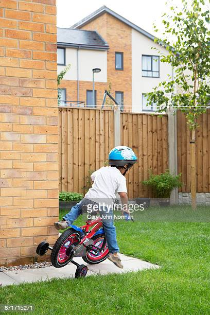 Young boy learning to ride bicycle in garden