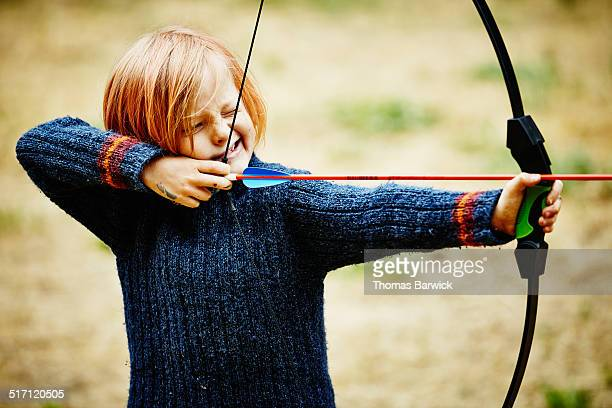 Young boy learning to shoot bow and arrow