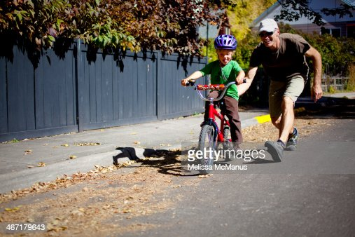 Young boy learns to ride bike