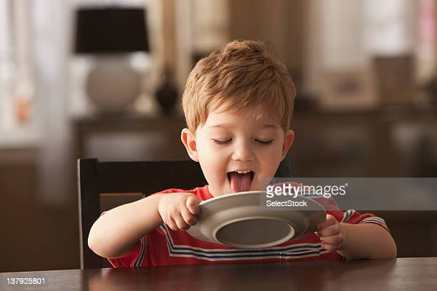 Young boy licking plate
