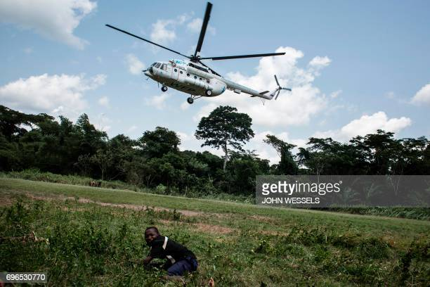TOPSHOT A young boy lies on a field as an helicopter carrying medical supplies and health workers specialised in Ebola virus takes off on June 11...