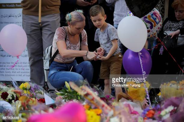 <> A young boy lights a candle in St Ann's Square on May 24 2017 in Manchester England An explosion at Manchester Arena on the night of May 22 as...