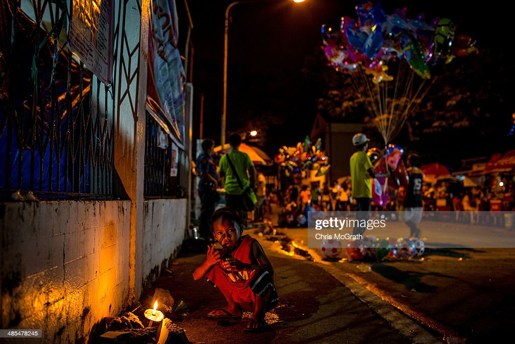 A young boy lights a candle on the street after watching the Procession of the Santo Entierro on April 18, 2014 in Tacloban, Leyte, Philippines. People continue to rebuild their lives five months after Typhoon Haiyan struck the coast on November 8, 2013, leaving more than 6000 dead and many more homeless. Although many businesses and services are functioning, electricity and housing continue to be the main issues, with many residents still living in temporary housing conditions due to 'No Build' areas preventing them from rebuilding their homes. This week marks Holy Week across the Philippines and will see many people attending religious activities.