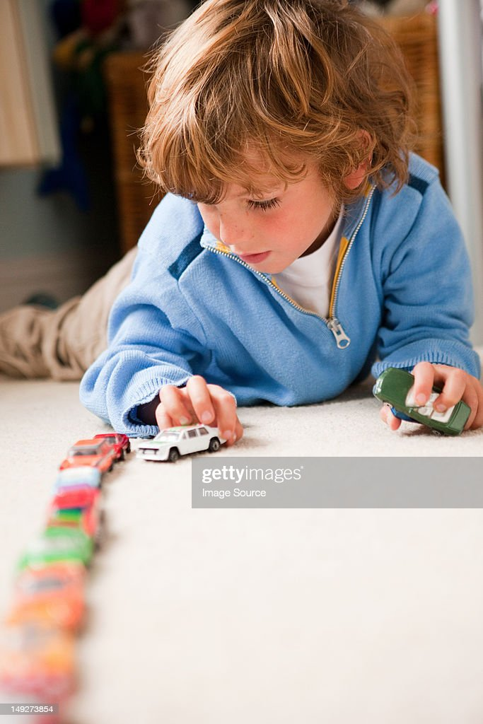 Young boy lining up toy cars in his bedroom : Stock Photo