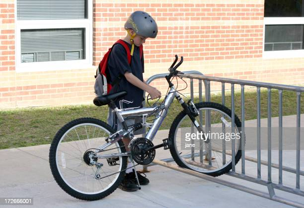 Young boy locks up his silver bike before going to school