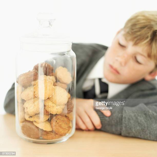 Young boy (12-13) looking at a jar of cookies