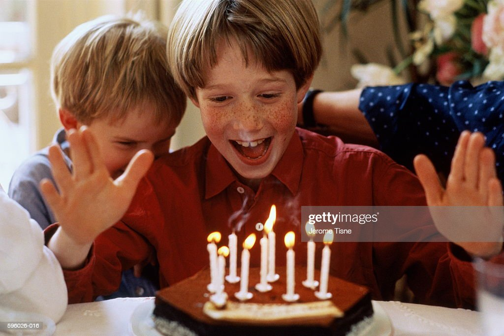 Young boy (8-9) looking at birthday cake with expression of delight : Stock Photo