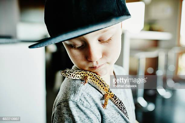 Young boy looking at pet gecko resting on shoulder