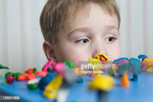 A young boy looking at various shapes made from child's play clay