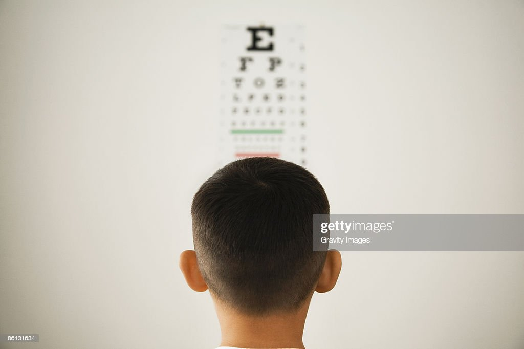 Young boy looking at wall eye chart : Stock Photo