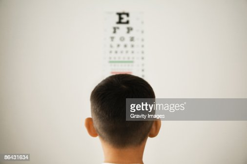 Young boy looking at wall eye chart : Foto de stock