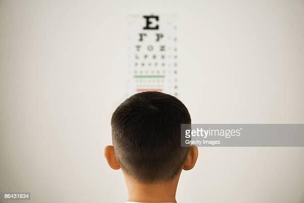 Young boy looking at wall eye chart