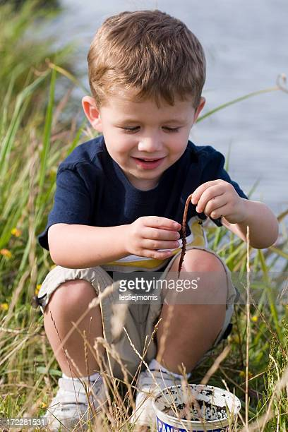 Young boy looking at worm crouching