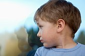 Young boy looking back at shadow in glass