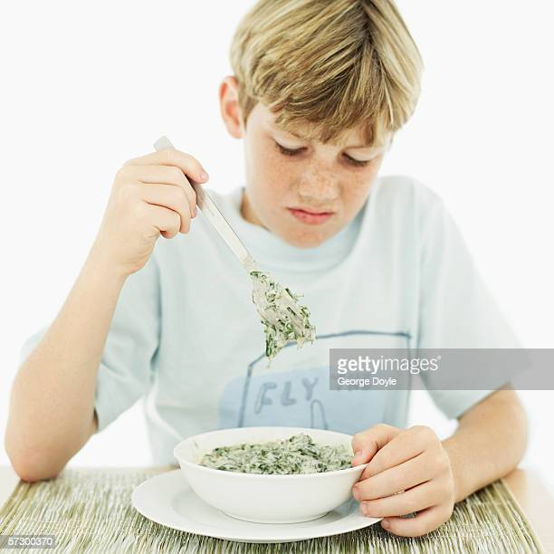 Young boy (12-13) looking down at a bowl of vegetable soup