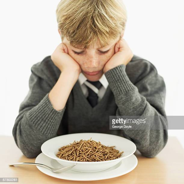 Young boy (12-13) looking down into a bowl of breakfast cereal