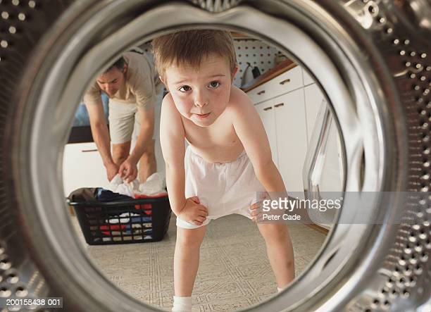 Young boy (4-6) looking inside washing machine,  father in background