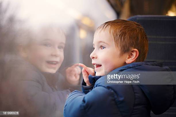 Young boy looking out of a train window