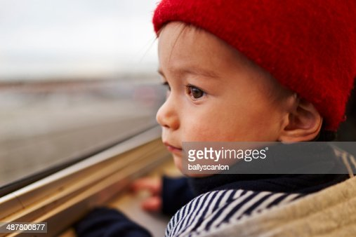 Young boy looking out train window